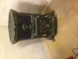 Vieux petit poêle céramique fonte